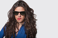 Portrait of sensuous young woman wearing sunglasses while biting lip over gray background