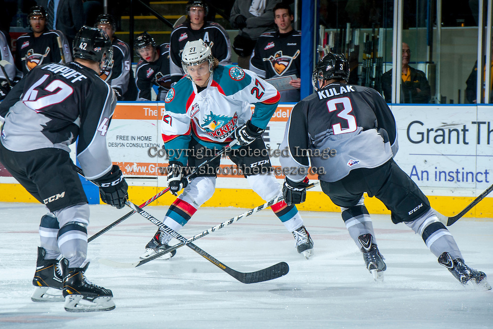 KELOWNA, CANADA - JANAURY 4: Ryan Olsen #27 of the Kelowna Rockets takes a shot while checked by Brett Kulak D #3 of the Vancouver Giants on January 4, 2014 at Prospera Place in Kelowna, British Columbia, Canada.   (Photo by Marissa Baecker/Shoot the Breeze)  ***  Local Caption  ***