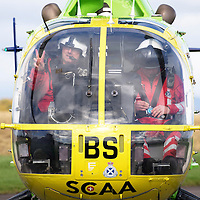 National Air Ambulance Week.. Britain's last Bolkow helicopter air ambulance operated by SCAA prepares to fly into history when it is replaced by EC-135 in November 2015. To mark this Scotland's original Bolkow paramedics gathered at Perth Airport to meet the current crew.<br /> Pictured Captain Russell Myles Senior Pilot, looks out of the Bolkow after getting a 999 callout during the photocall<br /> Picture by Graeme Hart.<br /> Copyright Perthshire Picture Agency<br /> Tel: 01738 623350  Mobile: 07990 594431