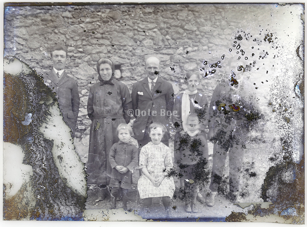 severely eroding glass plate with three generation of family posing