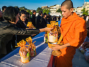 "20 JANUARY 2017 - BANGKOK, THAILAND: Buddhist monks collect alms from people during a ""tak bat"" (alms giving ceremony) on the plaza in front of Bangkok's City Hall. Hundreds of municipal workers and civil servants made merit by praying and presenting alms to 89 Buddhist monks Friday to mark 100 days of mourning since the death of revered Bhumibol Adulyadej, the Late King of Thailand. The significance of 89 monks is that the King, who died on October 13, 2016, was a few weeks short of his 89th birthday.        PHOTO BY JACK KURTZ"