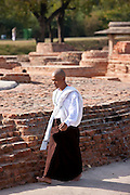 Buddhist monk praying as he walks around Dharmarajika Stupa at Sarnath ruins near Varanasi, Benares, Northern India