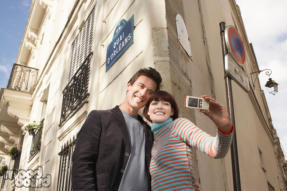 France Paris Couple taking self portrait on camera phone in front of apartment block