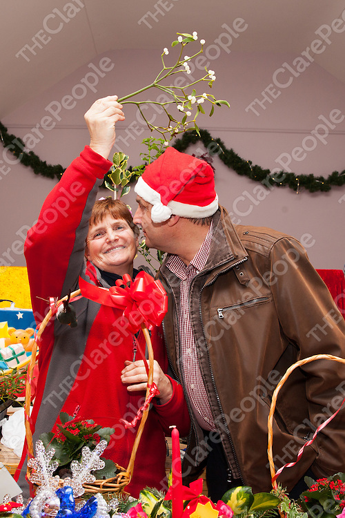 Maureen Roche and Frank Benson, both from the Ballyvaughan Farmers Market under the miseltoe at the Ballyvaughan Christmas Fair