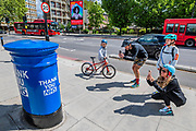 A family pauses thie bike ride to take pictures - One of  a handful of Royal Mail Letter boxes painted blue as a thank you to the NHS, outside St Thomas' Hospital. The 'lockdown' continues for the Coronavirus (Covid 19) outbreak in London.