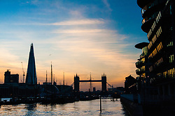 London, March 10th 2015. The sun sets over London after a warm early spring day. PICTURED: Modern apartments line the side of the River Thames as two Iconic London landmarks, Tower Bridge and THe Shard form a backdrop to the Dutrch Sailing Barges at the residential Hermitage Moorings in Wapping.
