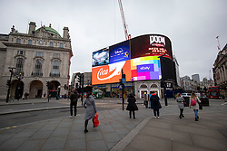 © Licensed to London News Pictures. 19/03/2020. London, UK. Pedestrians walk through Picadilly Circus as the Coronovirus outbreak escalates in London. The government has announced a series of measures designed to slow the spread of the virus, which is now spreading more rapidly in the capital than in other parts of the country. Photo credit: Rob Pinney/LNP