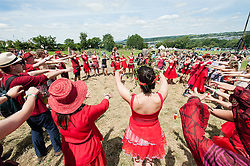 © Licensed to London News Pictures. 24/06/2015. Pilton, UK.   At Glastonbury Festival members of the Shakti Choir conduct an opening ceremony at the Stone Circle where the choir collective singing with the invention of reenergising the stones.  It is a warm sunny afternoon on  Wednesday Day 1 of the festival.        The pedestrian gates to the festival opened at 8am this morning, with many festival goers arriving and waiting throughout last night for the opening.  This years headline acts include Kanye West, The Who and Florence and the Machine, the latter having been upgraded in the bill to replace original headline act Foo Fighters.  Photo credit: Richard Isaac/LNP