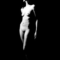 Nude woman poses against black background