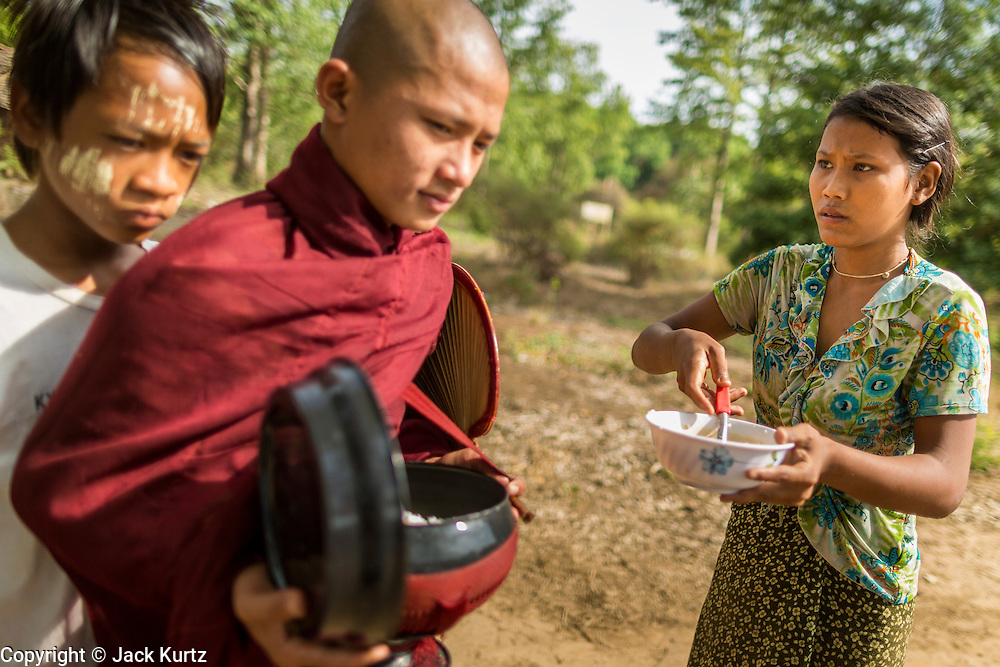 25 MAY 2013 - MAE SOT, TAK, THAILAND:  A Burmese woman waits to give food to Burmese novices in an unofficial village of Burmese refugees north of Mae Sot, Thailand. They live on a narrow strip of land about 200 meters deep and 400 meters long that juts into Thailand. The land is technically Burma but it is on the Thai side of the Moei River, which marks most of the border in this part of Thailand. The refugees, a mix of Buddhists and Christians, settled on the land years ago to avoid strife in Myanmar (Burma). For all practical purposes they live in Thailand. They shop in Thai markets and see their produce to Thai buyers. About 200 people live in thatched huts spread throughout the community. They're close enough to Mae Sot that some can work in town and Burmese merchants from Mae Sot come out to their village to do business with them.   PHOTO BY JACK KURTZ