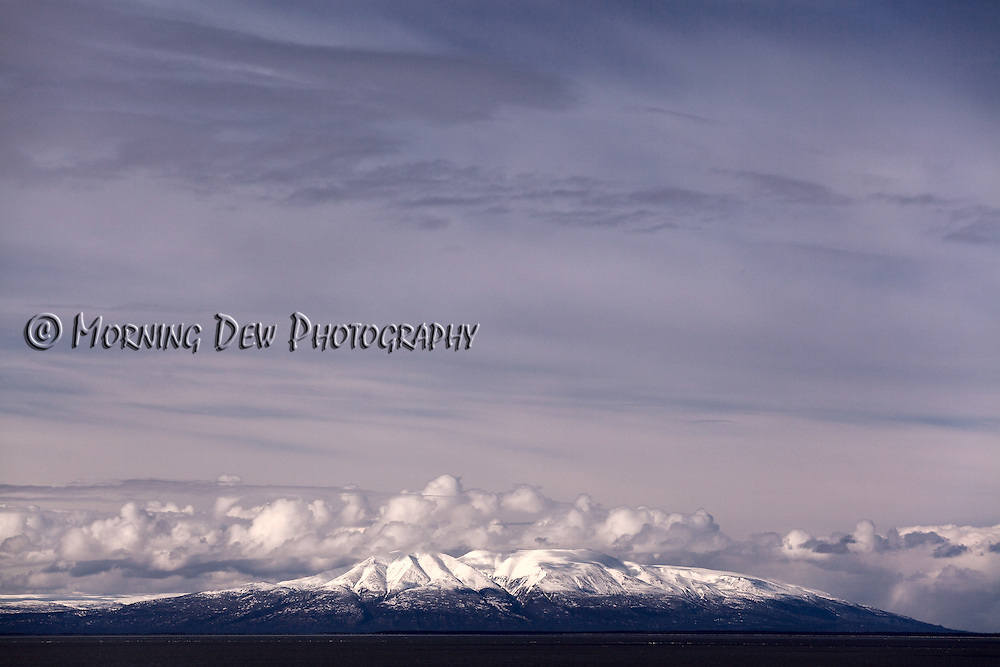 Early spring rain clouds cling the summit of Mount Susitna. Viewed from the Tony Knowles Coastal Trail, Anchorage, Alaska