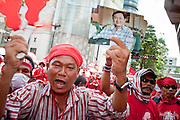 """Apr 4, 2010 - BANGKOK, THAILAND: A Red Shirt holds up a photo of deposed former Thai Prime Minister Thaksin Shinawatra in front of Gaysorn Plaza, one of Bangkok's most exclusive shopping malls, Sunday Apr. 4. Thousands of members of the United Front of Democracy Against Dictatorship (UDD), also known as the """"Red Shirts"""" and their supporters moved their anti government protests into central Bangkok Apr. 4 when they occupied Ratchaprasong intersection, the site of Bangkok's fanciest shopping malls and several 5 star hotels. The Red Shirts are demanding the resignation of current Thai Prime Minister Abhisit Vejjajiva and his government. The protest is a continuation of protests the Red Shirts have been holding across Thailand. They support former Prime Minister Thaksin Shinawatra, who was deposed in a coup in 2006 and went into exile rather than go to prison after being convicted on corruption charges. Thaksin is still enormously popular in rural Thailand. This move, away from their traditional protest site in the old part of Bangkok, has gridlocked the center of the city and closed hundreds of stores and restaurants and several religious shrines. There has not been any violence, but the government had demanded that the Red Shirts return to the old part of the city.   PHOTO BY JACK KURTZ"""