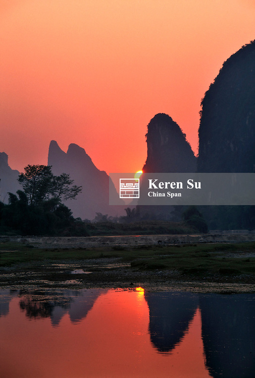 Landscape of Li River with reflection of karst hills in the water at sunset, Yangshuo, Guangxi Province, China