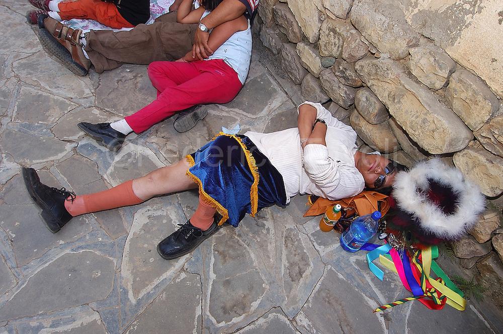 Bolivia. Tarija. Festa di San Roque..The many hours of dancing procession needs a break.