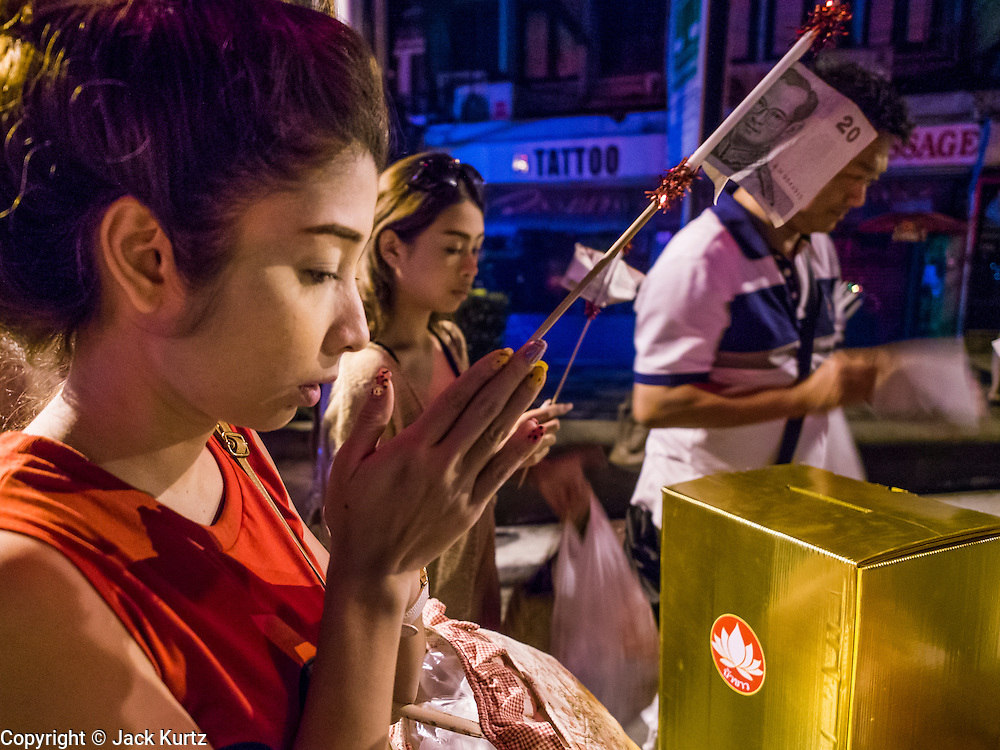 08 SEPTEMBER 2013 - BANGKOK, THAILAND:  A woman prays before donating money at a mass alms giving ceremony in Bangkok Sunday. 10,000 Buddhist monks participated in a mass alms giving ceremony on Rajadamri Road in front of Central World shopping mall in Bangkok. The alms giving was to benefit disaster victims in Thailand and assist Buddhist temples in the insurgency wracked southern provinces of Thailand.       PHOTO BY JACK KURTZ