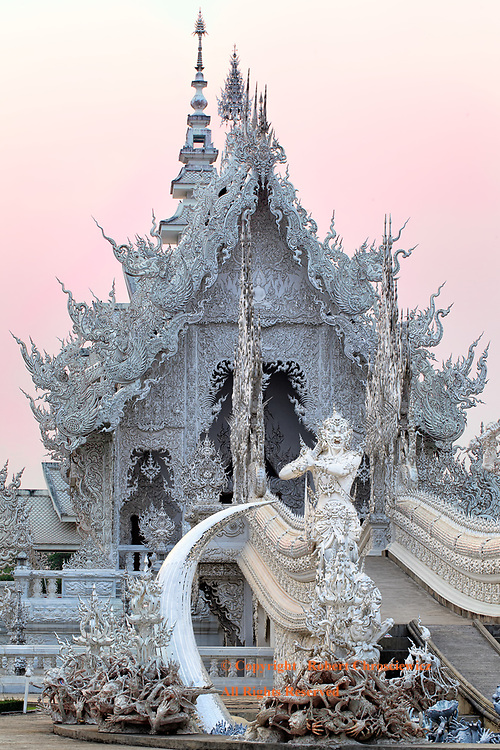 White Temple Sunset: Gremlins, soldiers and mystical guardians stand before the bridge that rises over the horror of hell on the path to Nirvana, Wat Rong Khun (the White Temple), Chiang Rai Thailand.    <br />