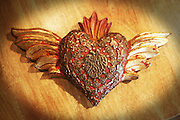 """Mexican handicrafts heart with milagritos or miracles. The heart is made on wood and is decorated with tiny metal figures best known as """"milagros"""" or """"milagritos"""" - meaning miracles. Milagros are an old Mexican tradition, meaning thanks for the gifts of heaven."""