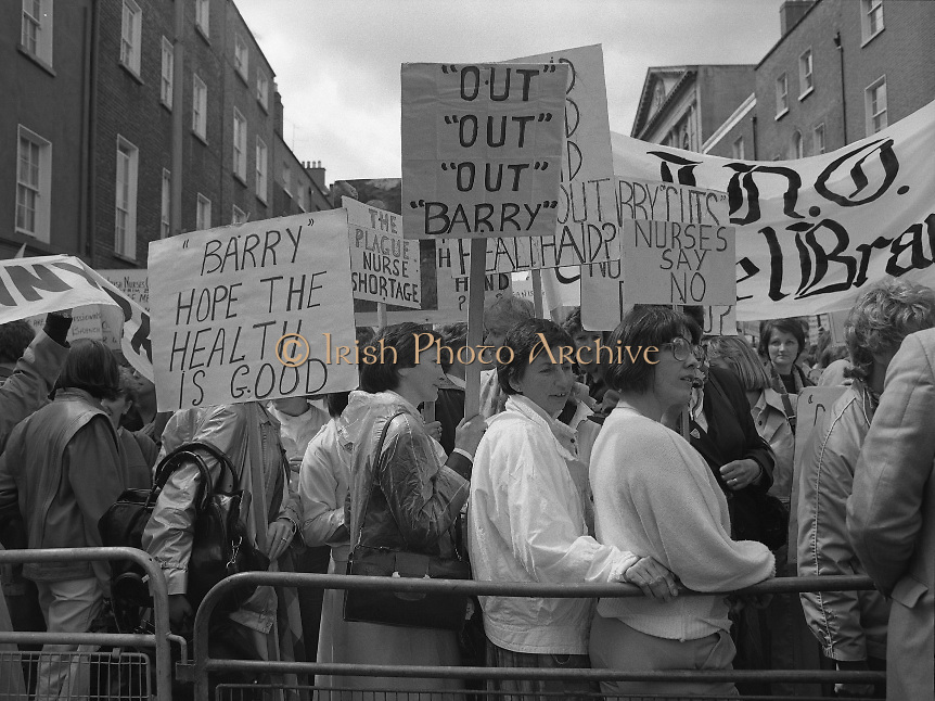 """Irish Nurses Organisation Protest..28.05.1986..05.28.1986..28th May 1986..In protest against proposed health cuts the Irish Nurses Organisation organised a protest march to Dail Eireann. Nurses from all over Ireland were represented at the march...Image shows nurses gathering at the barrier in front of Leinster House. The """"Barry"""" referred to on the placards is the Minister for Health Mr Barry Desmond TD."""