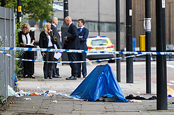 London, August 28 2017. Detectives and uniformed police work as a body lies covered in  Camden, North London following a stabbing in broad daylight at 11.45am. © Paul Davey.London, August 28 2017. as McDonalds workers from Cambridge and Crayford stage their first ever strike, supported by the Bakers, Food and Allied Workers Union, demanding more secure hours and better pay at a rally outside Parliament. © Paul Davey.