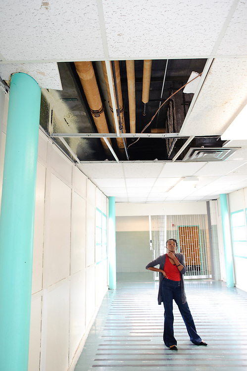 (photo by Matt Roth).Friday, May 14, 2010..Elani Odeyale, programming assistant to Baltimore Freedom Academy's principal, Khalilah Harris, stands under a massive ceiling hole in the hallway connecting to the gym. When it rains, this hole becomes a hazard. ..The building housing the Baltimore Freedom Academy, a grade 6-12 Baltimore public charter school focusing in social justice, was built in 1960. Fifty years later, the school is in disrepair. Old pipes make water from the fountains undrinkable. Asbestos makes repairing/replacing the pipes a hazard. The school has no air conditioning which makes the year-round school unbearable in the summer. The most derelict area is the boys locker room, where students are not allowed.