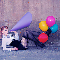 Young red head female wearing corset and stockings with clown make-up on eyes holding colorful balloons