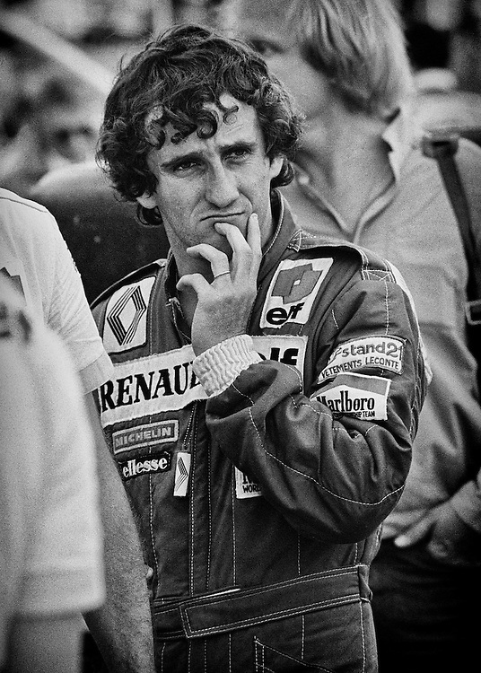 French driver Alain Prost contemplates changes to his Renault RE30B before qualifying for the 1982 Detroit Grand Prix.  He would go on to qualify on the pole and lead the race until electronic ignition problems would have him fall down the order to 11th at the finish. Prost had won the first two Grands Prix of the season, but then had three retirements and was desperate to ease team pressure and return to form. <br />