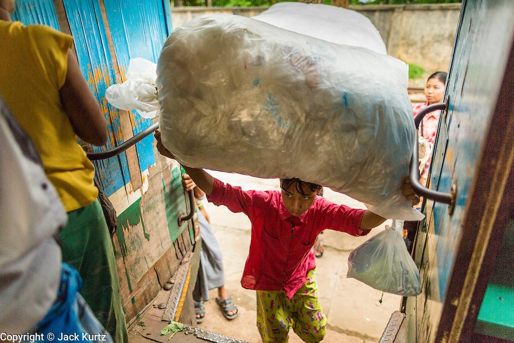 05 JUNE 2014 - YANGON, YANGON REGION, MYANMAR: A woman boards the Yangon Circular Train while she balances plastic bags on her hear. The Yangon Circular Train is a commuter train that circles Yangon, Myanmar (Rangoon, Burma). The train is 45 kilometers long, makes 38 stops and takes about three hours to make a loop of the city.     PHOTO BY JACK KURTZ