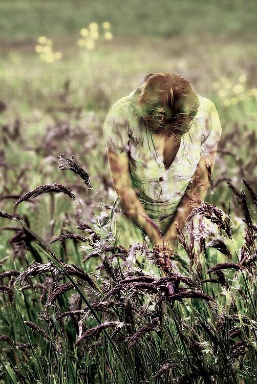 A woman kneeling in a grassy meadow