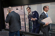 Londoners walk past a closed shop poster featuring a businessman wearing a blue suit - a favoured style and colour of menswear in the City of London, the capital's financial district - aka the Square Mile, on 29th August 2018, in London, England.