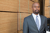Portrait of an African American businessman standing in front of stacked wooden planks