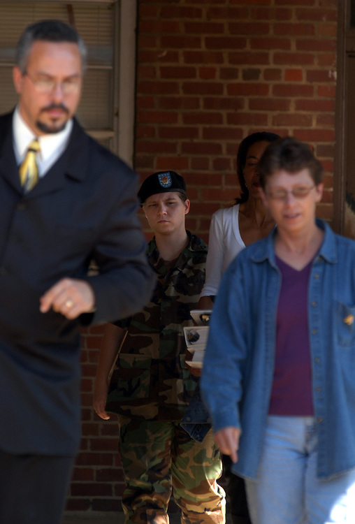 FORT BRAGG, NC- AUGUST 7: Pfc. Lynndie England leaves Saturday's hearing with her lawyer Rick Hernandez (L), defense investigator Kathleen Johnson, and her mother Terrie England at the Staff Judge Advocate Building on Fort Bragg in Fayetteville, NC on 8/7/04 for her Article 32 investigation hearing. England is charged with several counts, including one specification of conspiring to commit maltreatment of an Iraqi detainee, three specifications of assault against Iraqis, and several others. (Photo by Logan Mock-Bunting)