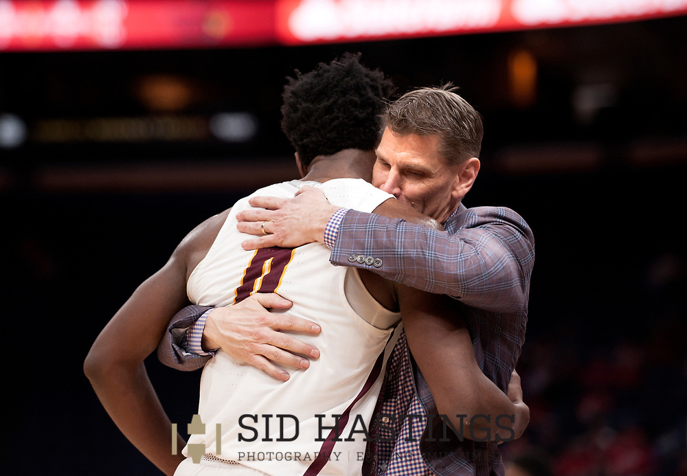 Loyola University Chicago player Donte Ingram (0) hugs coach Porter Moser after the Ramblers' topped Illinois State University 65-49 during the championship game of the Missouri Valley Conference men's basketball tournament at Scottrade Center in St. Louis Sunday, March 4, 2018. Photo © copyright 2018 Sid Hastings.
