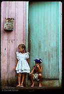 Young sister and brother hang out on front stoop of their home in jungle town of Eirunepe, AM Brazil