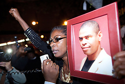 © Licensed to London News Pictures . 21/08/2012 . London , UK . Marcia Rigg , sister of Sean Rigg , who died in police custody in August 2008 , holds a photo of her dead brother and addresses protesters outside Brixton Police Station . Video has emerged of a man being detained on Sunday ( 19th August ) during which it is alleged police officers stamped on his head . Protesters marched to Brixton Police station and delivered a formal complaint about the incident . Photo credit : Joel Goodman/LNP
