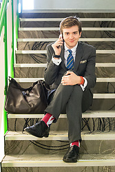 © Licensed to London News Pictures . 29/09/2017 . Torquay , UK . A delegate wearing Union Flag socks sits on stairs and makes a phone call . UKIP is due to announce the winner of a leadership election which has the potential to split the party . Photo credit: Joel Goodman/LNP