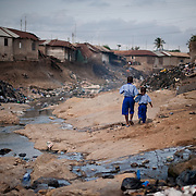 Two children make their way along the polluted gully that divides east and west Nima. Both sides of the community slope down to the river, washing trash and debris into the watercourse. In addition, in the absence of adequate waste collection and sanitation, the river serves as a de facto dumping ground and a latrine.