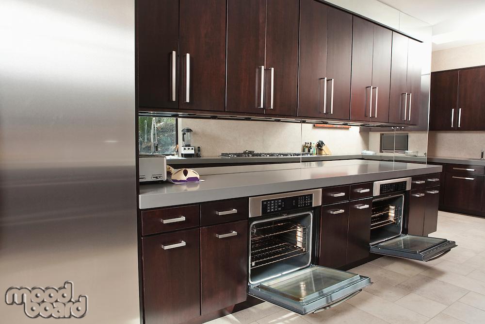 Dark wood kitchen with open oven doors