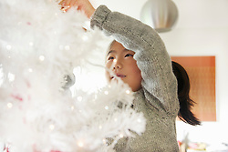 Close up of Young Girl Decorating Christmas Tree