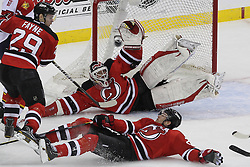 April 17, 2012; Newark, NJ, USA; New Jersey Devils goalie Martin Brodeur (30) makes a save while Florida Panthers center Marcel Goc (57) and New Jersey Devils defenseman Mark Fayne (29) battle during the first period of  game three of the 2012 Eastern Conference quarterfinals at the Prudential Center.