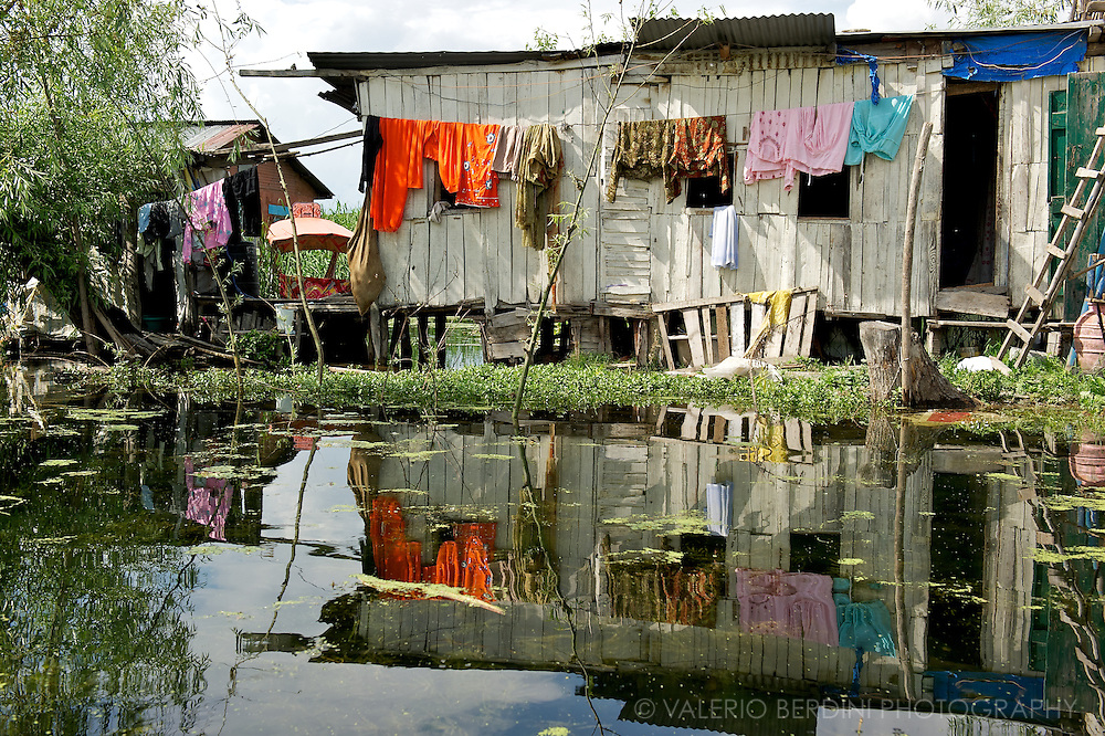 Clothes drying in front of a stilt house reflecting on the calm water of the Dal Lake. Srinagar. Kashmir. India