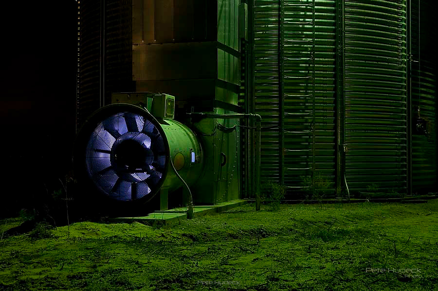 The burner of grain dryer at night with the green glow of a sodium vapor light