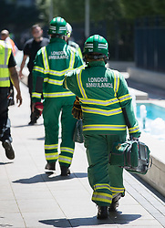 © Licensed to London News Pictures. 27/06/2018. London, UK. Paramedics attend flats on Queenstown Road, South London after a fire started. Attended by 58 firefighters,  the fire is reported to have started on a third floor balcony before working its way up the outside of the building. Photo credit: Peter Macdiarmid/LNP