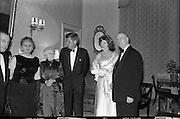 President John F. Kennedy entertained at a dinner party given by President Éamon de Valera at Áras an Uachtaráin. Included in the group are An Taoiseach Seán Lemass, Mrs de Valera and Mrs Eunice Shriver.