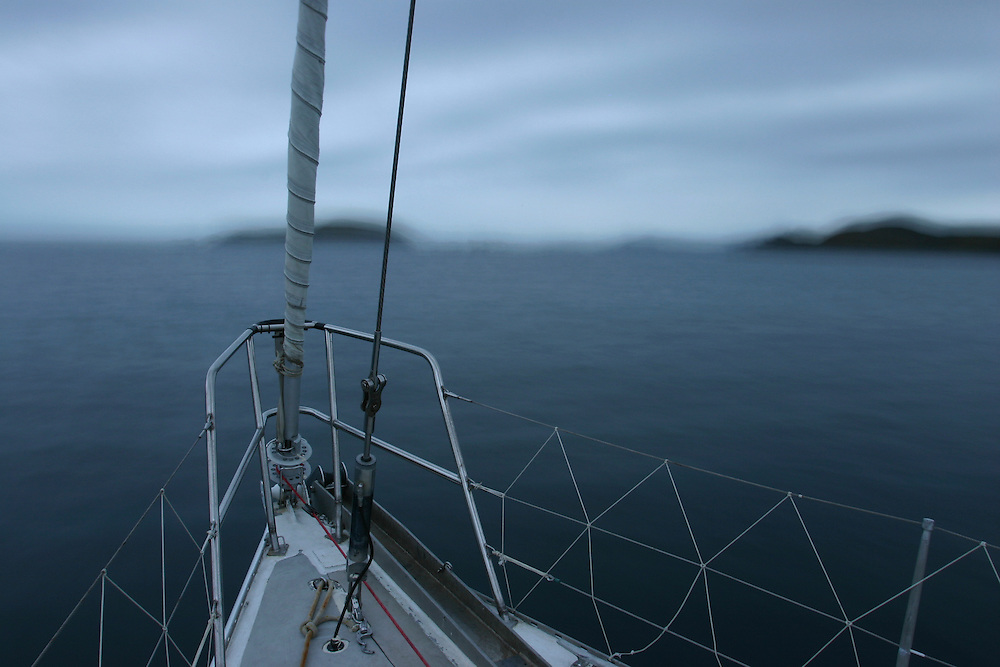 Chile, Isla Hornas. Bow of S/V Spirit of Sydney sailing south through small islands approaching Cape Horn at dusk