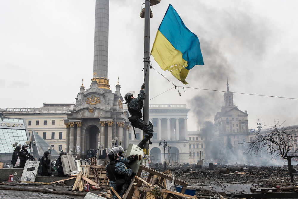 KIEV, UKRAINE - FEBRUARY 19: Berkut riot police hang a Ukrainian flag from a street light on Independence Square on February 19, 2014 in Kiev, Ukraine. After several weeks of calm, violence has again flared between anti-government protesters and police as the Ukrainian parliament is meant to take up the question of whether to revert to the country's 2004 constitution. (Photo by Brendan Hoffman/Getty Images) *** Local Caption ***