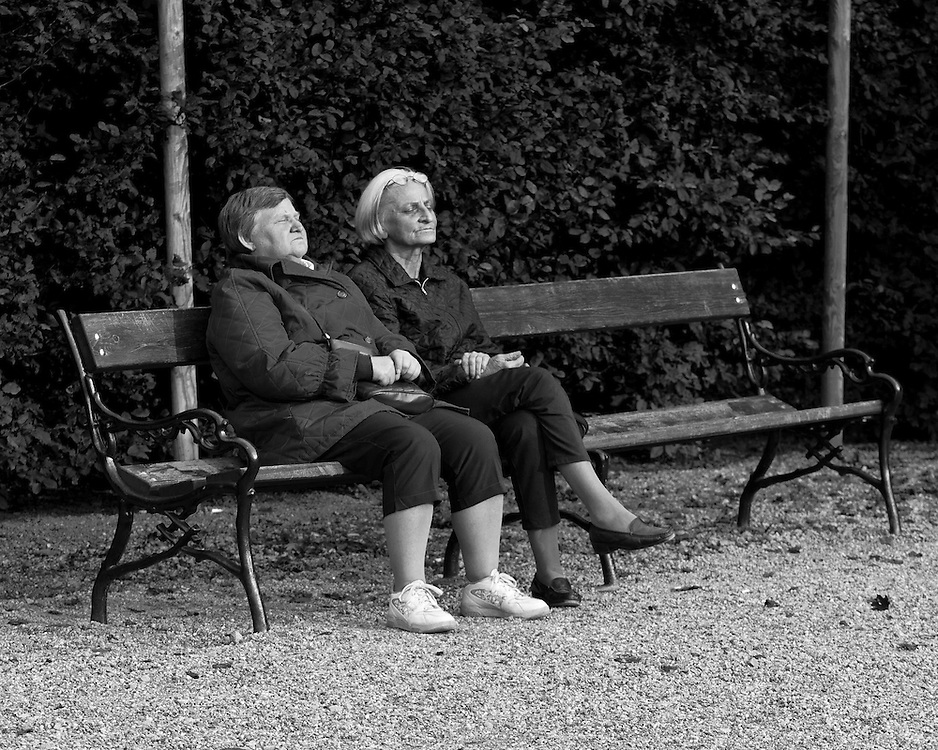 Elderly women resting with eyes closed on a park bench in the gardens of Schönbrunn Palace.