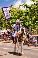 A paniolo, Hawaiian cowboy, mounted on his highly decorated horse promenades down Front Street as he represents Kauai in the annual King Kamehameha Day Parade in Lahaina, Hawaii.