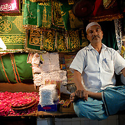 "A shop keeper selling souvenirs and offerings to the pilgrims at Nizamuddin Dargah, the mausoleum of Delhi's most famous Sufi saint Nizamuddin Auliya. It is visited daily by many people of all religions. The tomb of Amir Khusro is also located within the Nizamuddin Dargah Complex..The neighborhood of Delhi where the mausoleum is located is called ""Hazrat Nizamuddin"" or simply ""Nizamuddin"" because of this."
