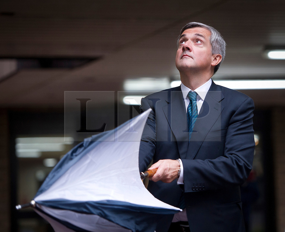 © London News Pictures. 01/10/2012. London, UK. Liberal Democrat MP CHRIS HUHNE putting up an umbrella as he leaves Southwark Crown Court at lunch time on October 1, 2012 where he faces charges of perverting the course of justice. The trial of Former Energy Secretary CHRIS HUHNE and his ex-wife VICKY PRYCE is due to start tomorrow (Tues) following legal argument today (Mon). HUHNE is accused of asking his ex-wife VICKY PRYCE to take speeding points on his behalf in 2003. Photo credit : Ben Cawthra/LNP
