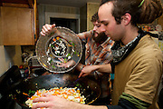 """November 3, 2010 - Brandon Bowser(front) and Ian Wexler(rear) stir fry vegetables at a house in Cambridge on Sunday in preparation of a Food Not Bombs meal in Central Square. The organization, which began in 1980 in Cambridge, provides free vegan meals to the public. According to literature, they """"rescue food that would otherwise go to waste."""" """"We rely on the pantry system,"""" said Jeff Reinhardt. Photo by Lathan Goumas."""